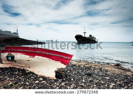 boat on the backgrond with old broken agrounded ship , Lanzarote, Canary Islands, Spain - stock photo