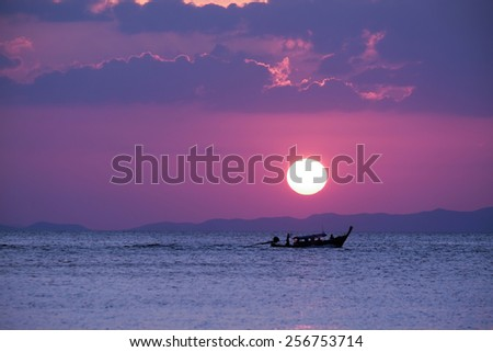 Boat on the ocean at sunset - stock photo