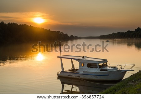 Boat on the river at dusk - stock photo