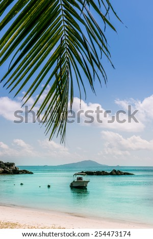 Boat on Tropical beach at Curieuse island Seychelles. Vertical shot - stock photo
