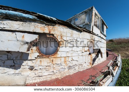 Boat out of water with paint peeling and boards falling off the boat - stock photo