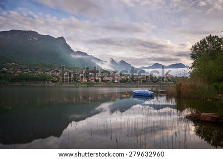 Boat over a quiet alpine lake in the morning