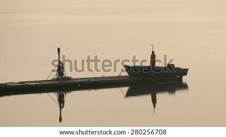 Boat, quay, water, fog, sunrise - stock photo