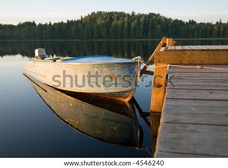 boat reflecting in calm waters of forest lake - stock photo