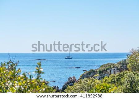 boat sailing by the coastline in Alghero, Sardinia - stock photo