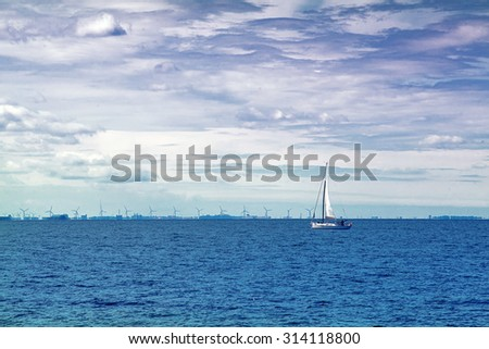 Boat Sailing on Open Blue Sea, Stormy Clouds at Sky, Uncertain Future Concept - stock photo