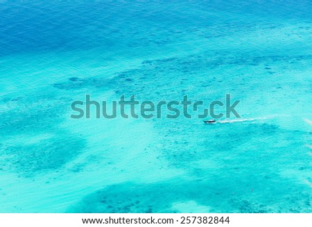 Boat sailing through the clear blue waters of a tropical island paradise in Thailand - stock photo