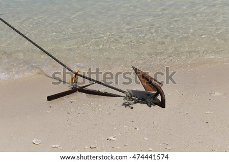 boat ship anchor on the beach with white sand and clam shell
