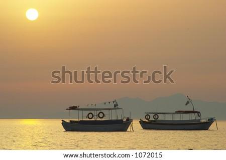 Boat silhouette at sunrise - stock photo