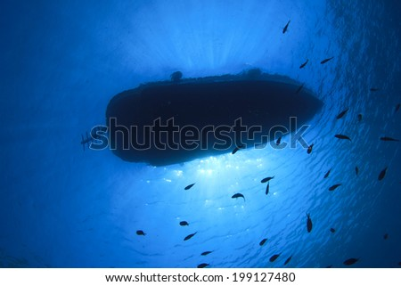 Boat silhouette from underwater with fish in blue sea - stock photo
