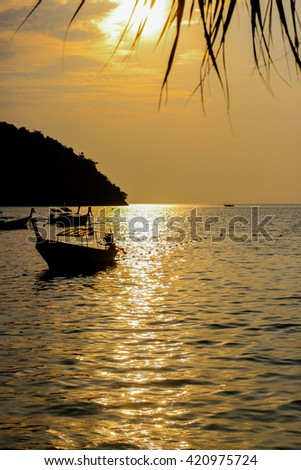 Boat silhouette in sunset light with island on background - stock photo