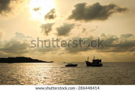 Boat silhouette in the sea against sunrise