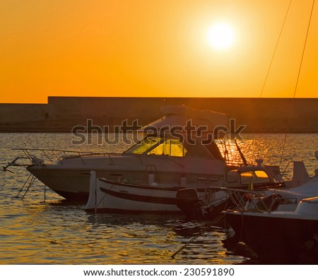 boat silhouettes in Alghero harbor at sunset