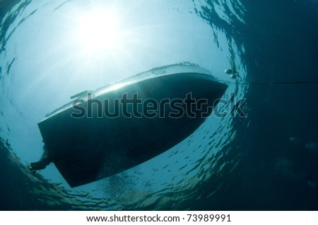 Boat silouetted by sun taken from under the water - stock photo