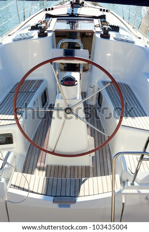 boat stern with big steering wheel and sailboat stern deck - stock photo