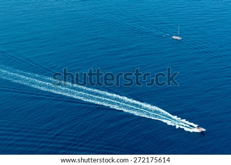 Boat surf foam aerial from prop wash in blue Majorca mediterranean sea - stock photo