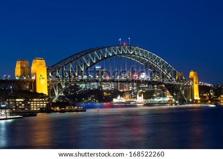 Boat traffic around Sydney harbour Bridge at rush hour on a winter's evening in Sydney, Australia - stock photo