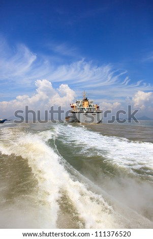 Boat wake and cargo ship to the sea - stock photo