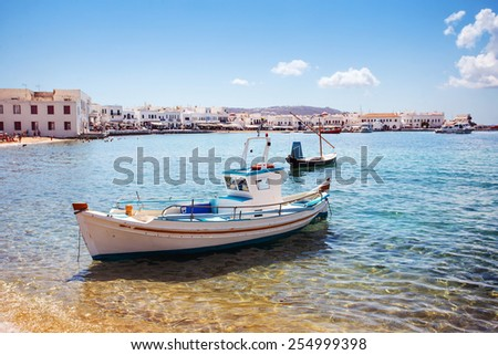 Boat with city of Mykonos in the background. Focus on boat. Greece. - stock photo