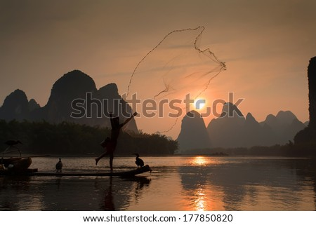 Boat with cormorants birds, traditional fishing in China use trained cormorants to fish, as well as cast net into the water. Yangshuo, China - stock photo