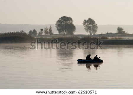 Boat with fishermen in the fog on the lake - stock photo