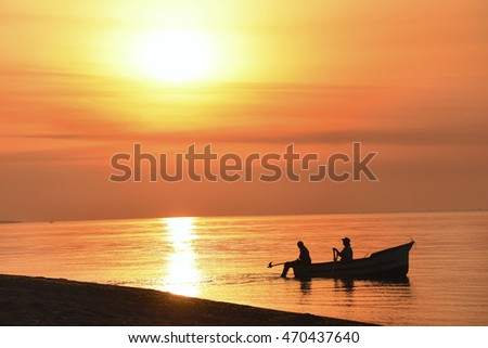boat with fishermen in the sea at sunrise, sunset. beautiful colorful sky and water with the reflection of light.  Seascape. dark silhouette of the boat with the fishermen in the sea at sunset, dawn.