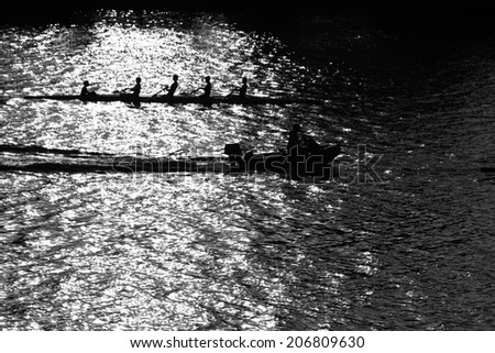 boat with four rowers and helmsman on river water - stock photo