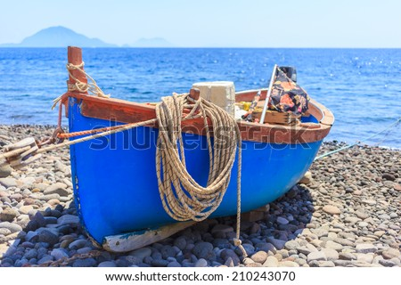 Boat, with hanging rope, docked on shore - stock photo
