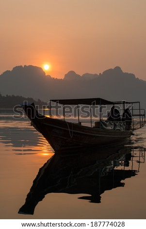Boat with sunrise at kayak on Rachapapha dam. Khao Sok National Park. Thailand. - stock photo