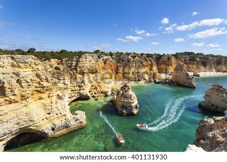 Boat with tourists visiting the caves near the beach ( praia da Marinha ), Algarve - stock photo