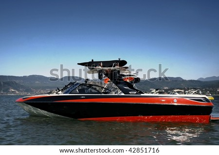 boat with wakeboard boards standing still on alake - stock photo