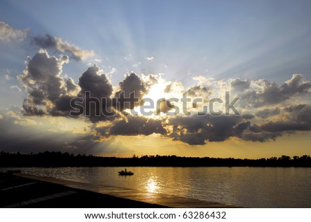 Boater on Lake at sunset in Northern Minnesota. - stock photo