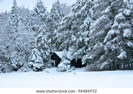 Boathouse along the shore is covered in snow - stock photo