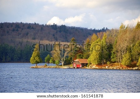Boathouse is highlighted by the morning sun at the start of a beautiful autumn day - stock photo