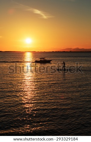 Boating and rafting activities at sunset - stock photo
