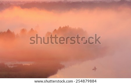 boatman in the fog on the river - stock photo