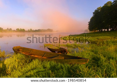 boats about the foggy sunrise on the river - stock photo