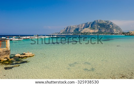Boats anchored in clear turquoise waters of Mondello with Palermo on background, Sicily, Italy.