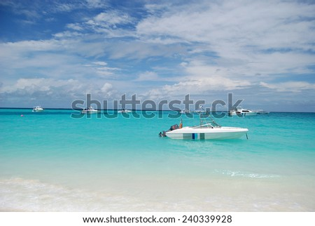 Boats anchored off Maldives on clean blue water.