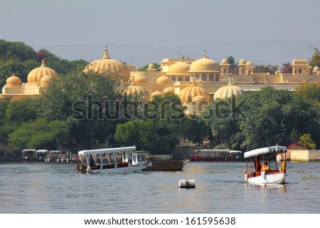 boats and palace on Pichola lake in Udaipur India - stock photo