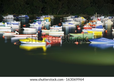 Boats and pier on river at night - stock photo