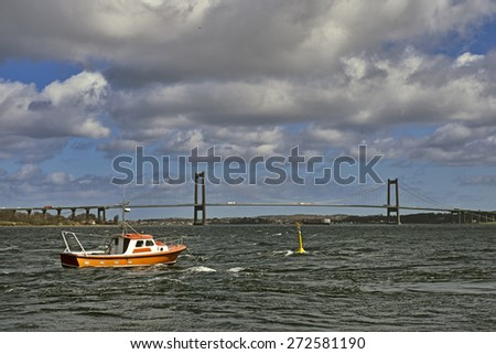 Boats and strong flowing water in Little Belt close to the bridge, Denmark. - stock photo