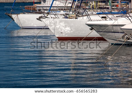 Boats and yachts in a marina, moored and stand on an anchor.