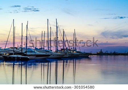 Boats and yachts in marina during sunset - stock photo