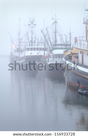 Boats at Dock, Fog, Steveston. Dense fog surrounds seine boats tied to the dock in Steveston Harbor near Vancouver. British Columbia, Canada.  - stock photo