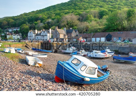 Boats at low tide in the harbour at Porlock Weir, a picturesque village on Exmoor National Park in Somerset - stock photo