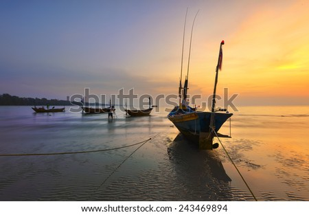 Boats at the beach during sunset.  - stock photo