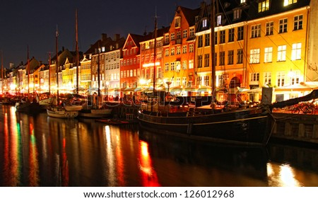 Boats at the Nyhavn harbor in night, Copenhagen, Denmark. Nyhavn is a famous 17th century embankment, canal and entertainment area in Copenhagen - stock photo