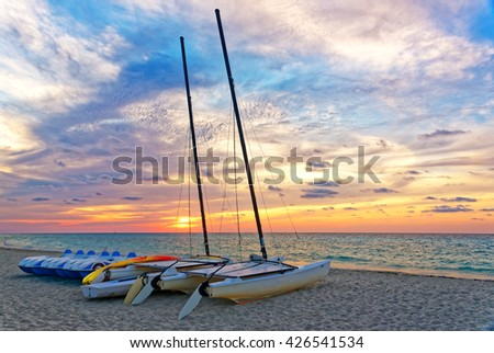 Boats, catamarans and pedal boats on the beach at sunset time - stock photo