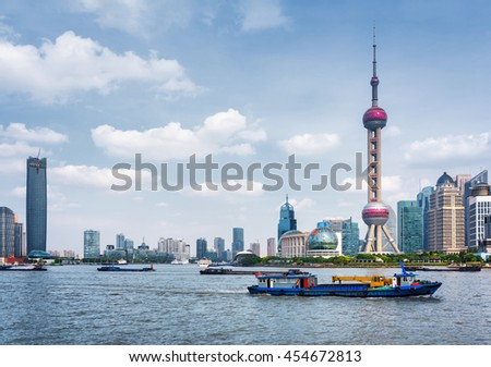 Boats crosses the Huangpu River in Shanghai, China. View from the Bund. The Oriental Pearl Tower is visible at right. Shanghai is a popular tourist destination of Asia and a global financial center.